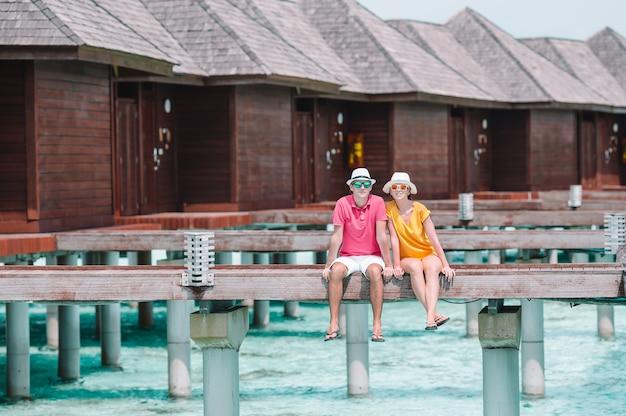 Jong koppel op strand steiger op tropisch eiland in huwelijksreis Premium Foto