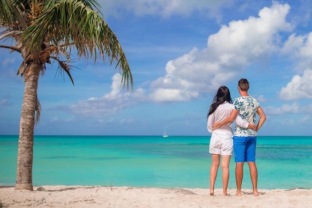 Jong koppel op wit strand tijdens zomervakantie. gelukkige familie geniet van hun huwelijksreis Premium Foto