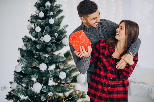 Jong koppel samen bij de kerstboom thuis Gratis Foto