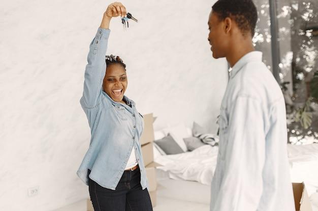 Jong koppel samen verhuizen naar nieuw huis. afrikaans amerikaans echtpaar met kartonnen dozen. vrouw houdt sleutels. Gratis Foto