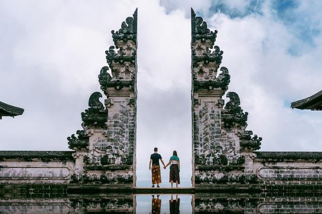 Jong koppel staande in tempel poorten en hand in hand van elkaar bij lempuyang luhur tempel in bali, indonesië. vintage toon Gratis Foto