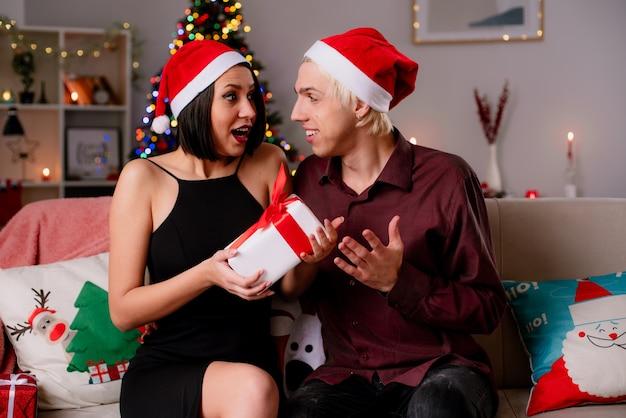 Jong koppel thuis in de kersttijd met kerstmuts zittend op de bank in de woonkamer kijken elkaar onder de indruk Gratis Foto