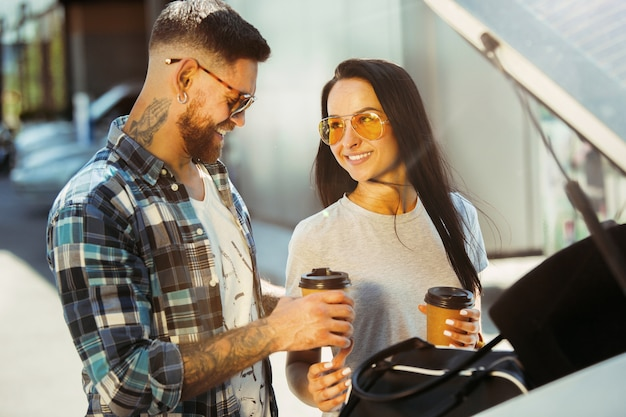 Jong koppel vakantie reis op de auto in zonnige dag voorbereiden. vrouw en man koffie drinken en klaar om naar zee of oceaan te gaan. Gratis Foto