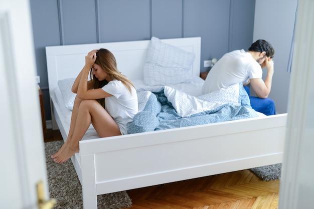 Jong koppel vechten in hun slaapkamer. ze zaten allebei aan de andere kant van het bed en zagen er verdrietig en teleurgesteld uit. Premium Foto