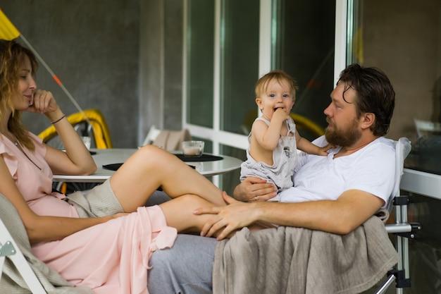 Jong koppel verliefd op een klein kind op het terras van zijn huis. Gratis Foto