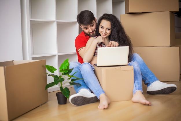 Jong koppel verplaatsen in een nieuw huis, zitten en ontspannen na het uitpakken, op zoek naar iets op laptop Premium Foto