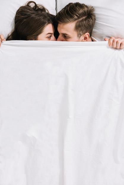 Jong koppel verstopt onder witte deken Gratis Foto