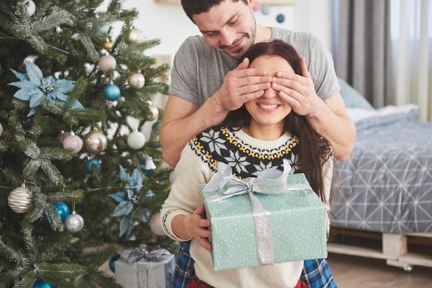 Jong koppel vieren kerstmis. een man presenteerde plotseling een cadeau aan zijn vrouw. het concept van gezinsgeluk en welzijn Premium Foto