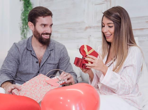 Jong koppel zittend op bed met geschenken Gratis Foto