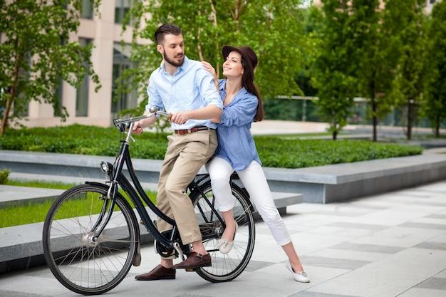 Jong koppel zittend op een fiets Gratis Foto