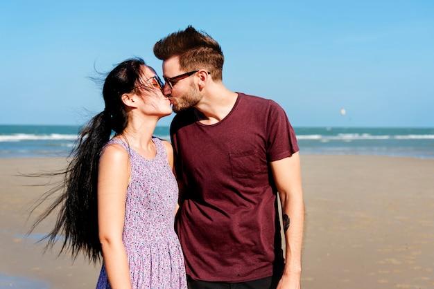 Jong koppel zoenen op het strand Premium Foto