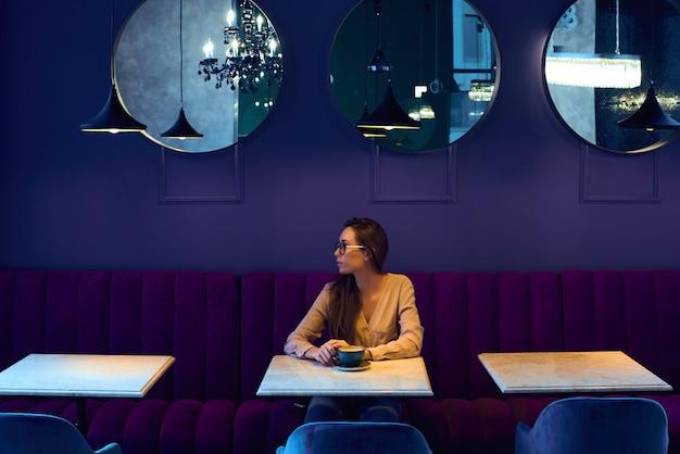 Jong lachend zakelijke vrouw zitten in cafe aan tafel, kijkt uit raam. op tafel staat een kopje koffie. Premium Foto