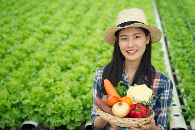 Jong landbouwersmeisje die divers van groenten in mand met glimlach houden Premium Foto