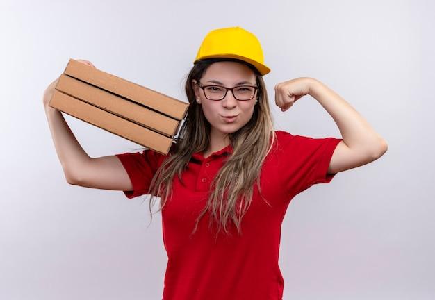 Jong levering meisje in rood poloshirt en gele pet met stapel pizzadozen die zich voordeed als een winnaar met biceps glimlachend zelfverzekerd Gratis Foto