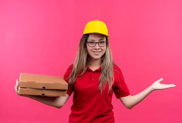 Jong levering meisje in rood poloshirt en gele pet met stapel pizzadozen presenteren met arm van haar hand glimlachen Gratis Foto