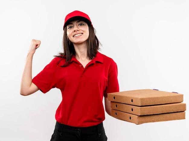 Jong leveringsmeisje die rood uniform en glb dragen die stapel pizzadozen vasthouden die vuist gelukkig en positief glimlachen die status over witte achtergrond balanceren Gratis Foto