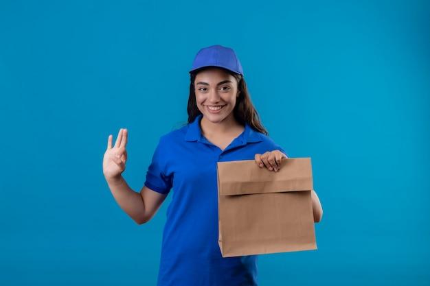 Jong leveringsmeisje in blauw uniform en glb die document pakket houden die vrolijk glimlachen doen ok teken dat zich over blauwe achtergrond bevindt Gratis Foto