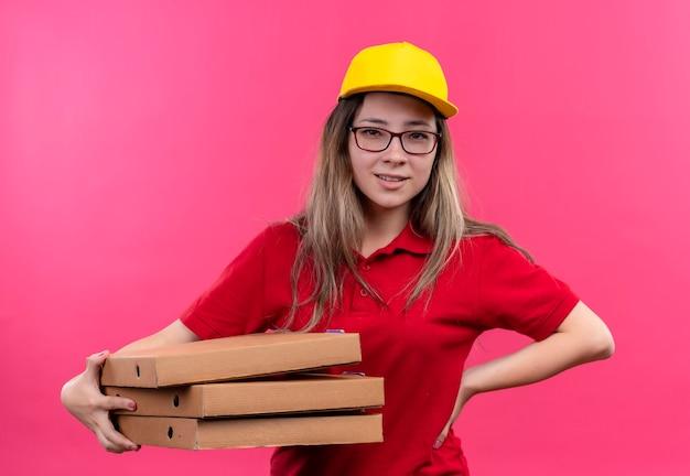 Jong leveringsmeisje in rood poloshirt en de gele stapel van de glbholding pizzadozen die er zelfverzekerd uitzien Gratis Foto