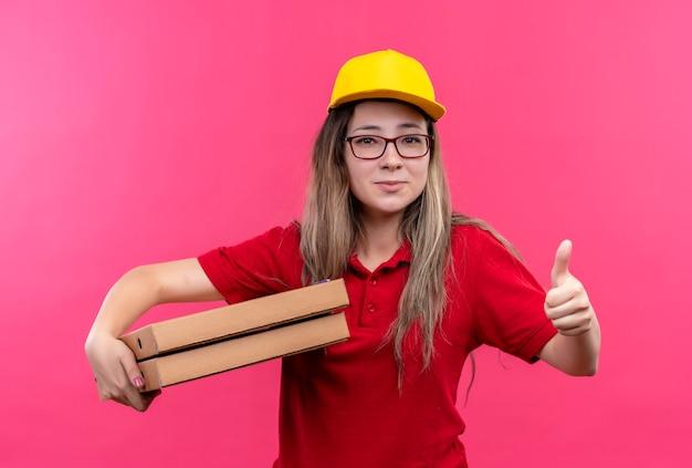 Jong leveringsmeisje in rood poloshirt en geel glb-holdingsstapel pizzadozen die het tonen duimen glimlachen Gratis Foto