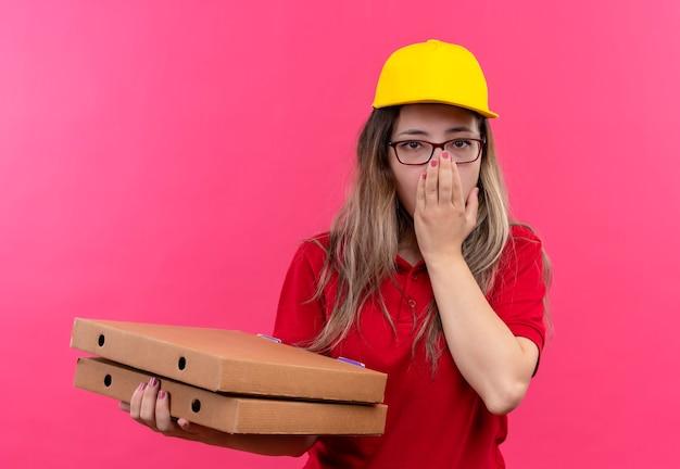 Jong leveringsmeisje in rood poloshirt en geel glb-holdingsstapel pizzadozen geschokt die mond met hand behandelen Gratis Foto