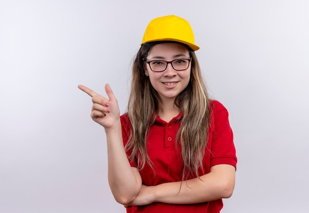 Jong leveringsmeisje in rood poloshirt en geel glimlachend vriendelijk wijzend met vinger naar de kant Gratis Foto