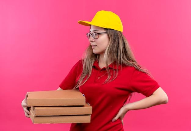 Jong leveringsmeisje in rood poloshirt en gele glb-holdingsstapel pizzadozen die opzij met zelfverzekerde uitdrukking kijken Gratis Foto