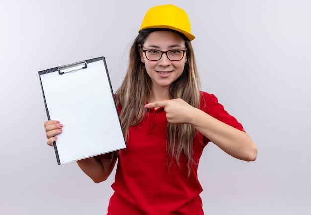Jong leveringsmeisje in rood poloshirt en gele pet die klembord met blanco pagina's tonen die met vinger ernaar wijzen Gratis Foto
