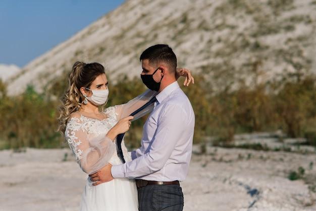 Jong liefdevol paar wandelen in medische maskers in het park tijdens hun trouwdag. Premium Foto