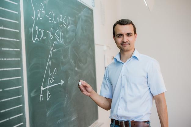 Jong mannelijk leraar of studentenholdingskrijt die op bord in klaslokaal schrijven Premium Foto