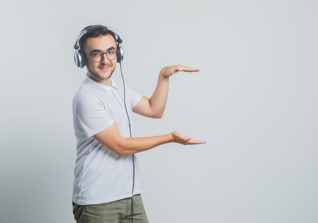 Jong mannetje dat grootteteken in wit t-shirt, broek toont en zelfverzekerd kijkt Gratis Foto