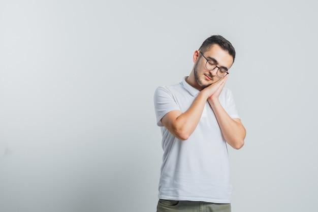 Jong mannetje dat op handpalmen als hoofdkussen in wit t-shirt leunt en mooi kijkt Gratis Foto