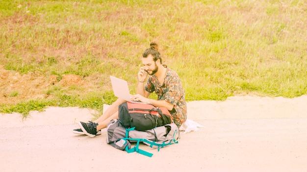 Jong mannetje dat op laptop surft en op telefoon in landelijk spreekt Gratis Foto