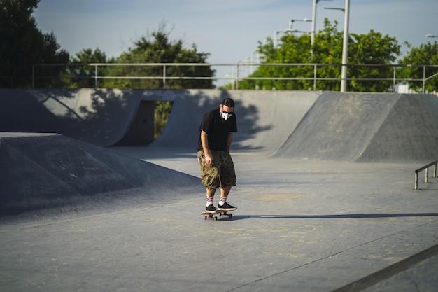 Jong mannetje dat verschillende trucs met een skateboard in het park doet dat een medisch gezichtsmasker draagt Gratis Foto