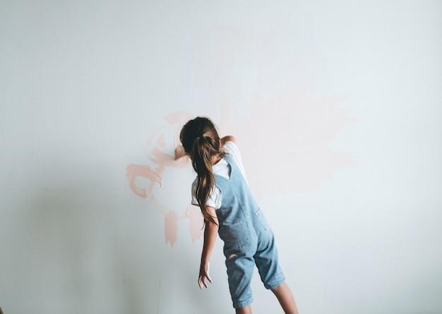 Jong meisje dat de muren roze schildert Premium Foto