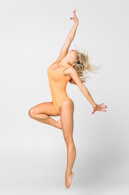 Jong meisje dat geïsoleerde gymnastiekoefening doet Gratis Foto