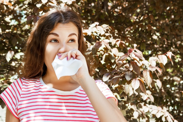 Jong meisje dat haar neus blaast. jong meisje met allergie in de herfstpark Premium Foto