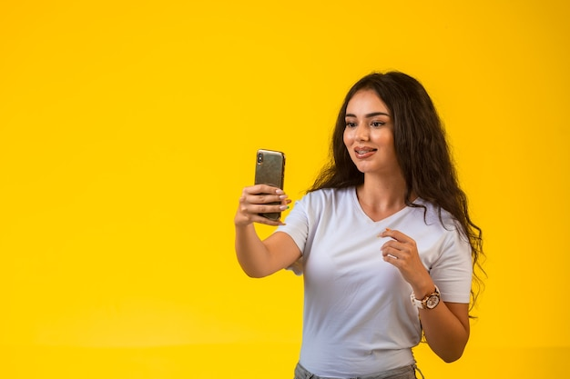 Jong meisje dat haar telefoon bekijkt en selfie neemt. Gratis Foto