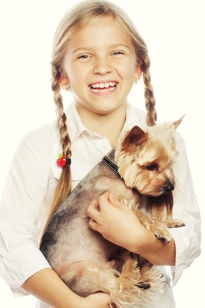 Jong meisje dat houdend een leuk puppy glimlacht Premium Foto