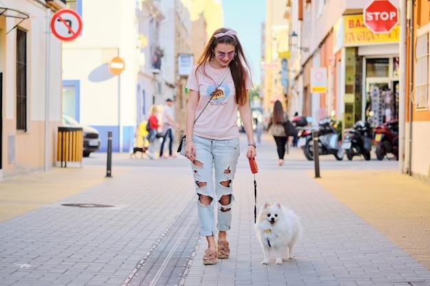 Jong meisje dat met een witte pluizige pomeranian loopt. Premium Foto