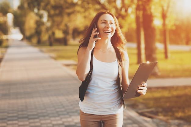 Jong meisje dat op een celtelefoon spreekt in het park Premium Foto