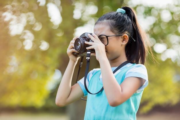 Jong meisje dat op een foto van camera klikt Premium Foto