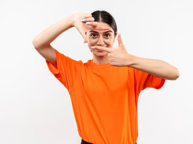 Jong meisje dat oranje t-shirt draagt dat frame met vingers door dit frame maakt glimlachend staande over witte muur Gratis Foto