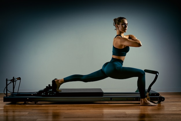 Jong meisje dat pilates oefeningen met een hervormerbed doet. mooie slanke fitnesstrainer op hervormer grijze achtergrond, low key, kunstlicht. fitness concept Premium Foto