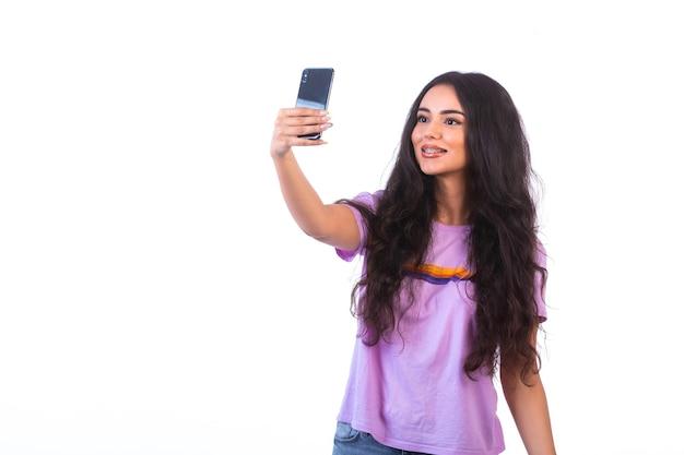 Jong meisje dat selfie met haar mobiele telefoon op witte muur neemt. Gratis Foto