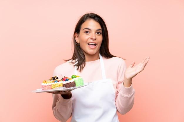 Jong meisje dat veel verschillende minicakes over geïsoleerde muur met geschokte gelaatsuitdrukking houdt Premium Foto