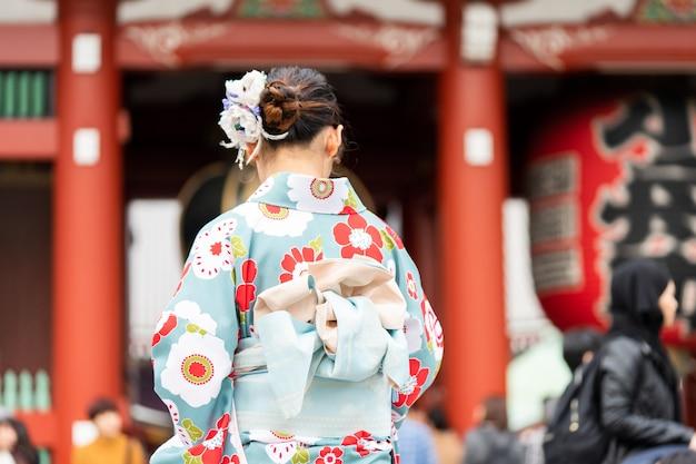 Jong meisje die japanse kimono dragen die zich voor sensoji-tempel in tokyo bevinden, Premium Foto
