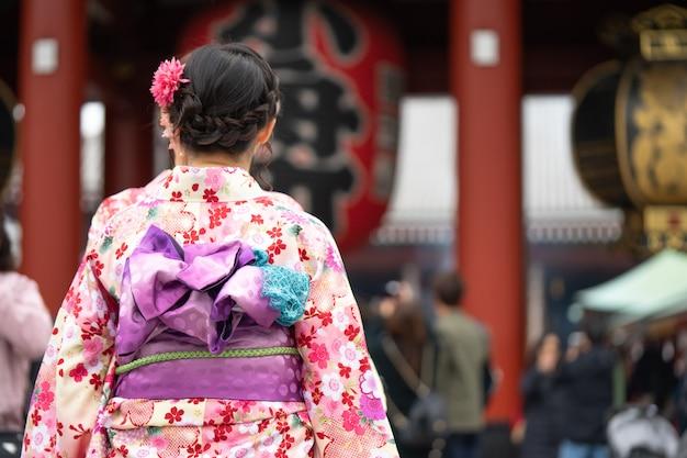 Jong meisje die japanse kimono dragen die zich voor sensoji-tempel in tokyo, japan bevinden. Premium Foto