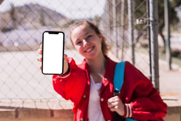 Jong meisje die smartphone in park tonen Gratis Foto