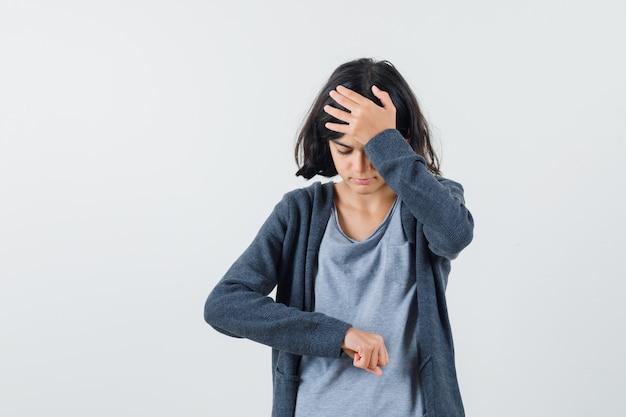 Jong meisje doet alsof ze naar de klok kijkt terwijl ze de hand op het voorhoofd legt in een lichtgrijs t-shirt en een donkergrijze hoodie met ritssluiting en er gestrest uitziet Gratis Foto