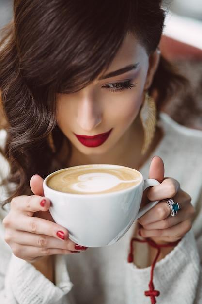 Jong meisje, drinken koffie in een trendy café Gratis Foto
